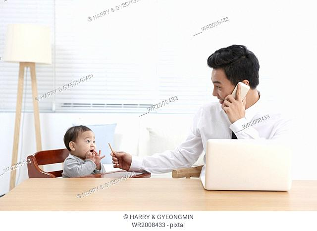 a business man at a table with a baby