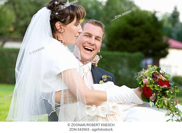 Lachender Bräutigam trägt seine Braut auf Händen