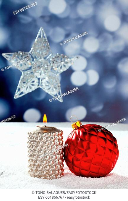 Christmas card of silver star bauble and candle on snow and blue background