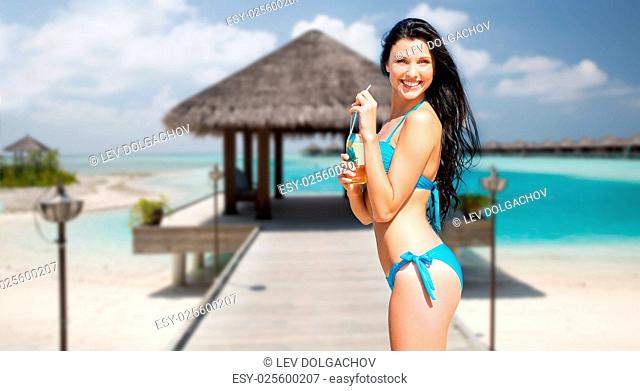 travel, tourism, summer holidays, vacation and people concept - happy beautiful woman with bottle of drink and straw over exotic tropical beach with bungalow...