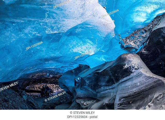 A couple poses for a picture inside a Canwell Glacier ice cave in the Alaska Range; Alaska, United States of America