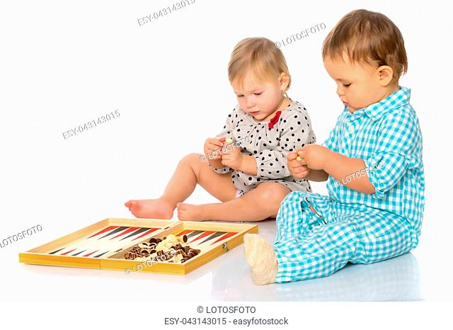 Baby boy and girl, play chess or backgammon. The concept of a harmonious development of a child in the family, a happy childhood
