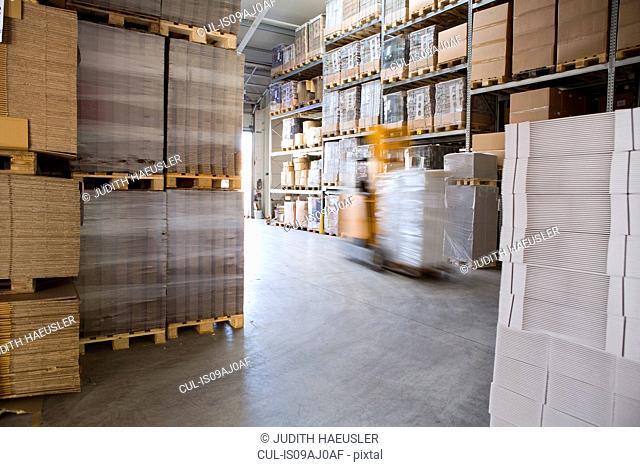 Blurred forklift truck in storage warehouse