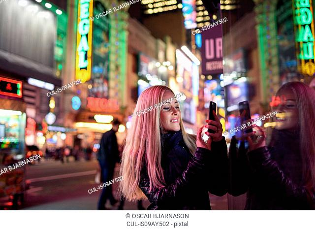 Female tourist taking smartphone selfie in Times Square at night, New York, USA