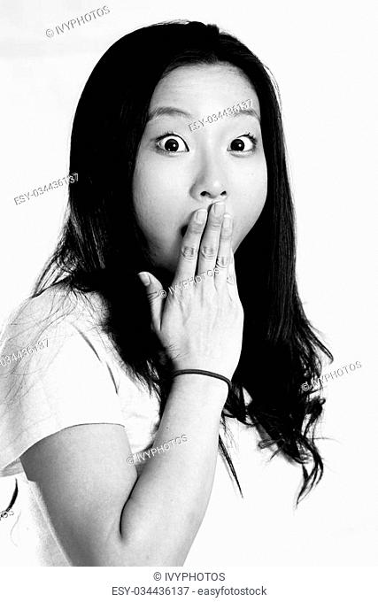 Portrait of young woman looking shocked and covering her mouth, black and white style