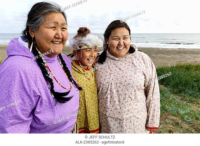 Portrait of Yupik Eskimo mother and daughters wearing traditional dress, in grass along Bering Sea shore, Nome, Alaska, Summer