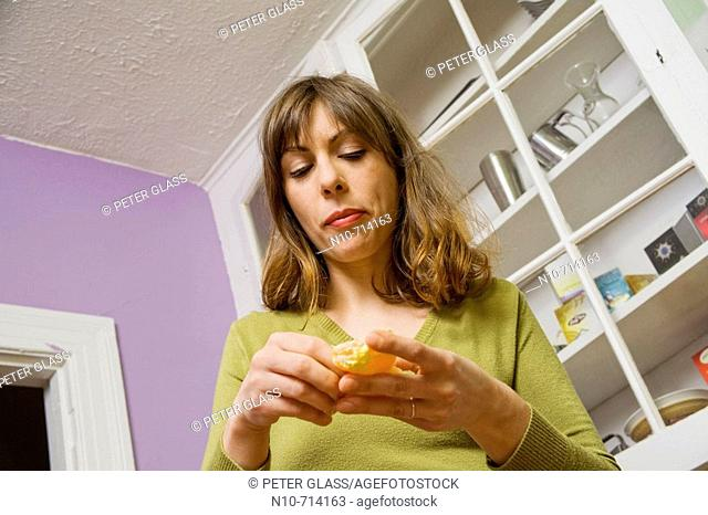 Young woman, in her kitchen, eating an orange