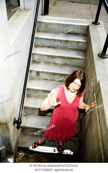 Young woman walking down a set of concrete stairs