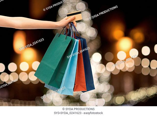 shopping bags and credit card in hand at christmas