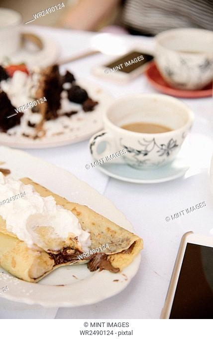 Close up of food and drink on a table, a hot drink, cake and pancake with cream
