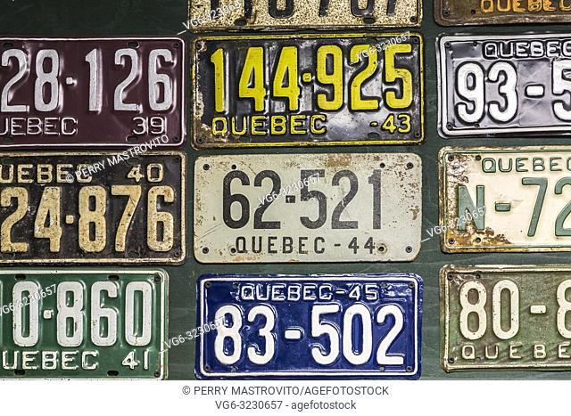 Colourful collection of vintage Quebec automobile licence plates on garage wall inside an old 1927 Canadiana cottage style home