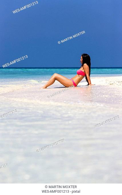 Maldives, Young woman in bikini sitting in shallow water