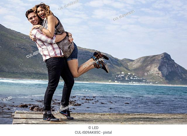 Young couple hugging on coastal pier, Cape Town, Western Cape, South Africa
