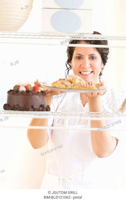 Hispanic baker holding fresh desserts