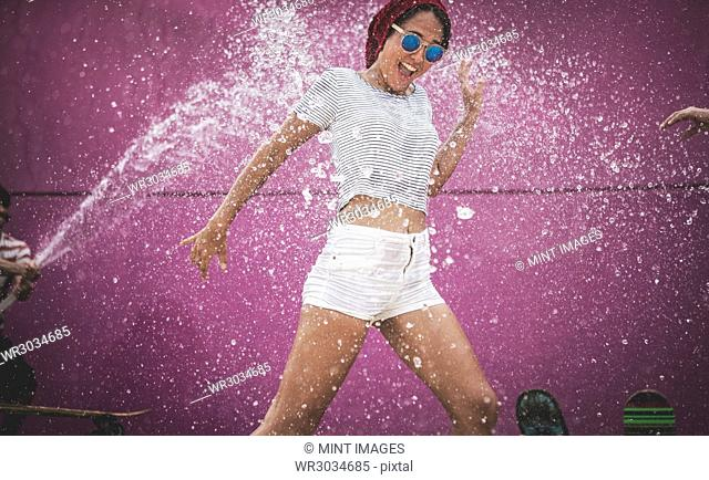 A young woman being sprayed with water