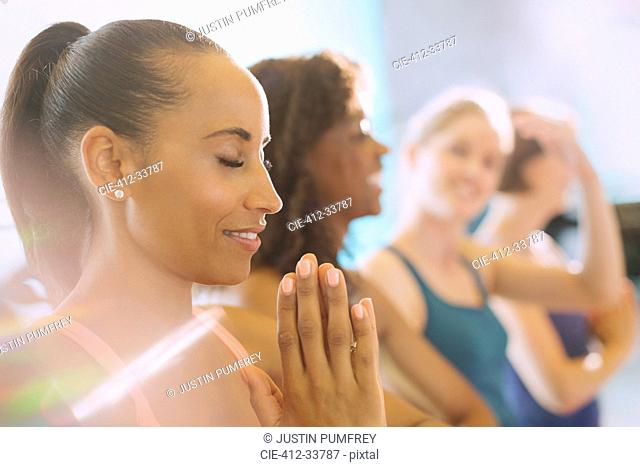 Serene woman practicing yoga with hands at heart center in gym studio