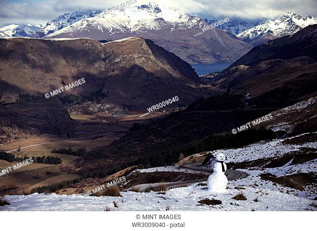 Mountain valley with snow-capped peaks and a lake in the distance, a snowman in the foreground