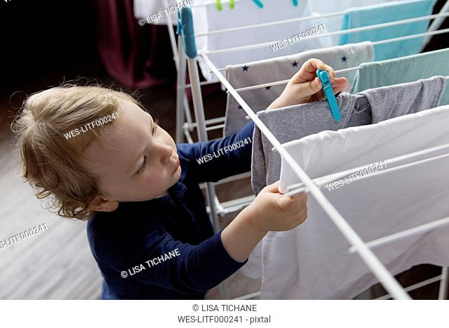 Little boy putting clothes peg on drying laundry