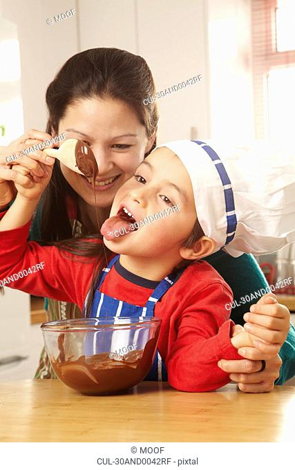 Boy licking chocolate off spoon with mum