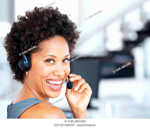 Closeup of attractive call center agent laughing while talking on headset