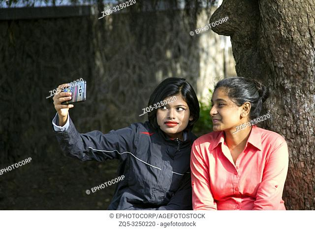 Two young Indian girls sitting and taking selfie with happy expression, Pune