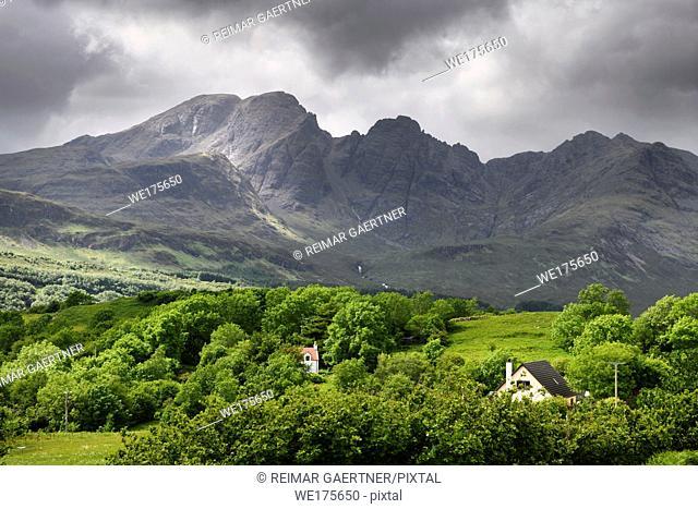 Sun on Bla Bheinn peak outlier of Black Cuillin Hills under dark clouds from Torrin Scottish Highlands Isle of Skye Scotland UK