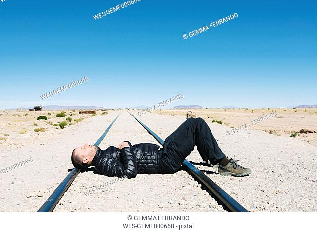 Bolivia, Uyuni train cemetery, man lying on train tracks