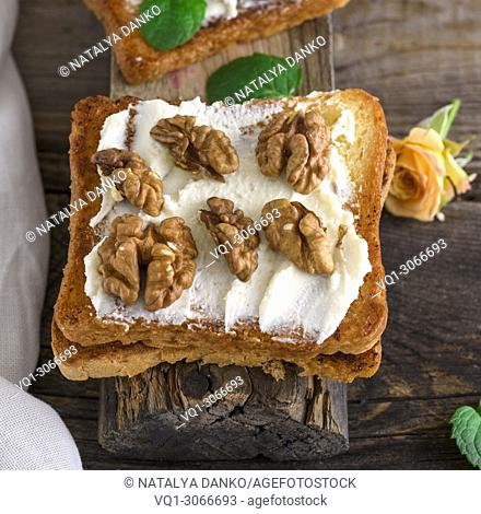 toast with mild cottage cheese and walnuts on a gray wooden board, top view