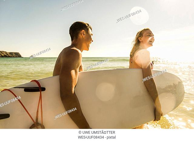 Teenage couple carrying surfboard at the sea