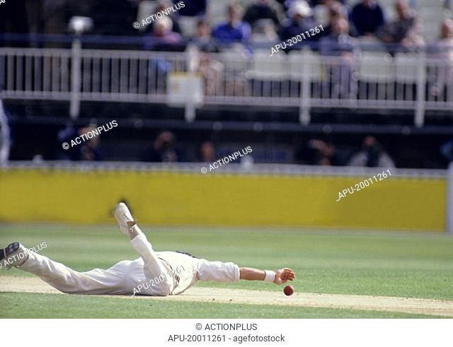 Cricketer diving for the ball