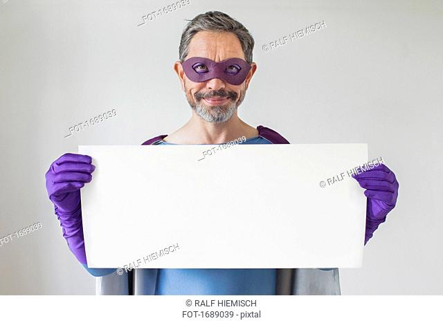 Portrait of superhero holding blank placard against white background