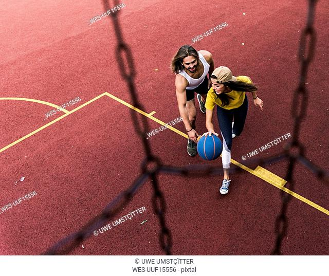 Young man and woman playing basketball on basketball ground