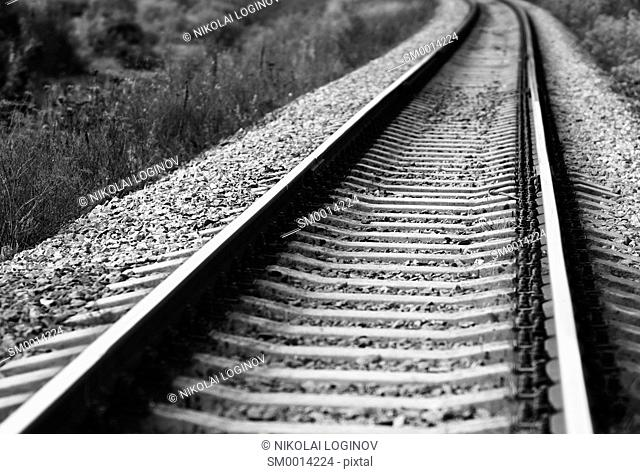 Diagonal black and white railroad track bokeh background