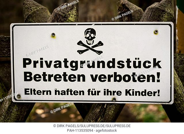 A white prohibition sign saying Private property. Enter prohibited! Parents are clinging to a hunter's fence somewhere in Berlin for their children with a skull...