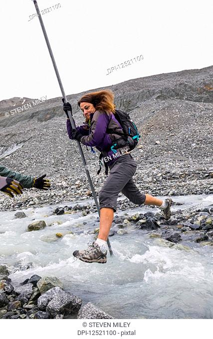 A woman jumps over a swift glacial stream with the aid of a pole near Gulkana Glacier; Alaska, United States of America