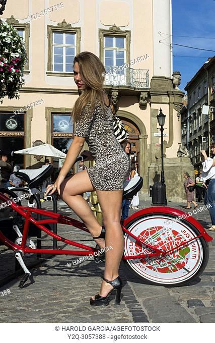 Sexy, slim and elegant Ukrainian woman wearing a leopard skin print suit posing on a red and white touring bike for a photographic sequence in the ancient city...