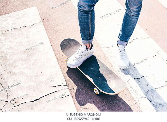 Legs and feet of young male skateboarder on pedestrian crossing