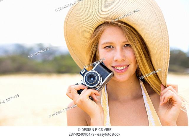 Beautiful Young Woman at the Beach with Vintage Camera