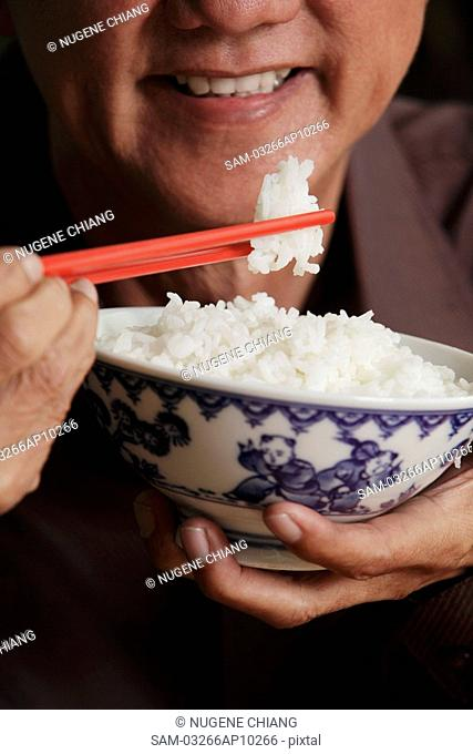 cropped shot of mature man holding chopsticks and bowl of rice