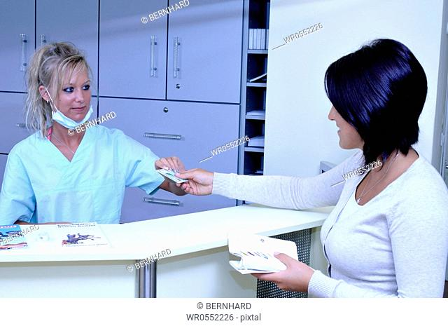 female patient and female medical assistant at the reception