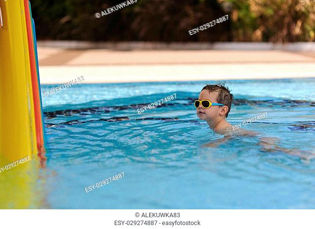 In the sunny day in the summer the boy in sun glasses floats in pool 6b8762a84