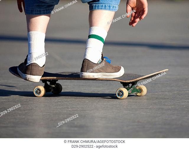 Skateboarding - detail of skateboard and legs with trainers