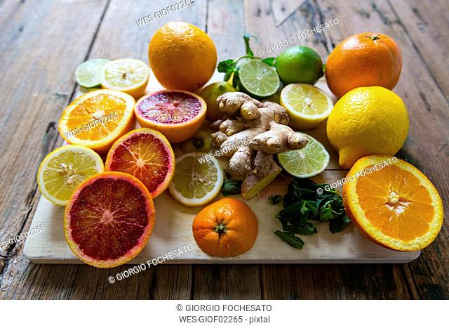 Sliced and whole lemons, oranges and limes, ginger root and mint leaves on wooden board