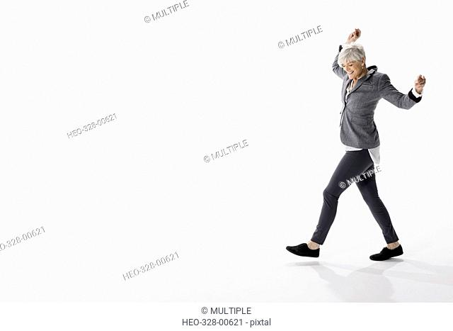 Energetic senior woman dancing against white background