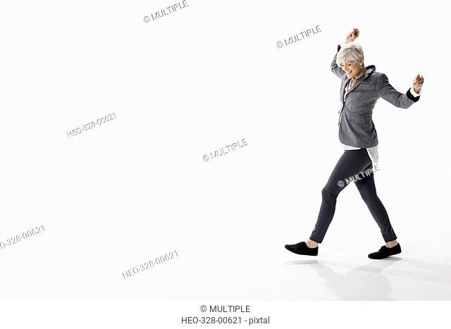 Energetic senior woman dancing against white background
