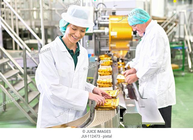 Worker stacking cheese on production line in cheese processing plant