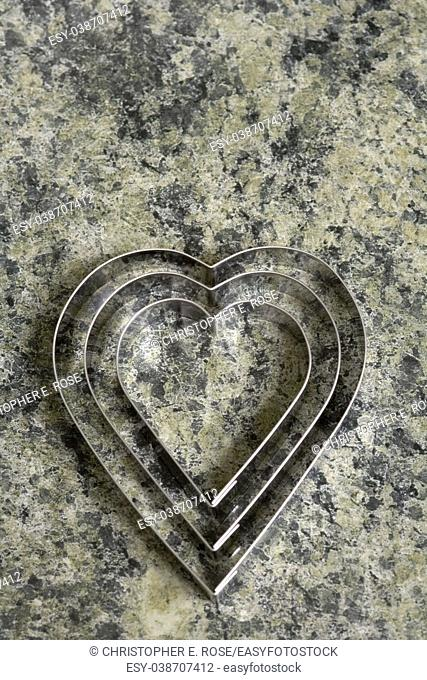 A set of three heart shaped cookie cutters on a marble effect kitchen surface