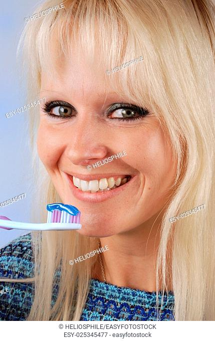 Young blonde woman brushing her teeth
