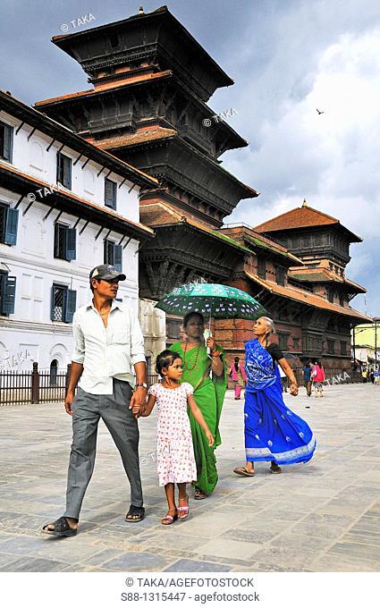 Family walking through Durbar Square  Temple behind is Basantapur Durbar in Hanuman Dhoka Durbar world heritage monument zone