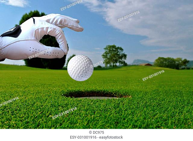 a man push a ball in a golf hole